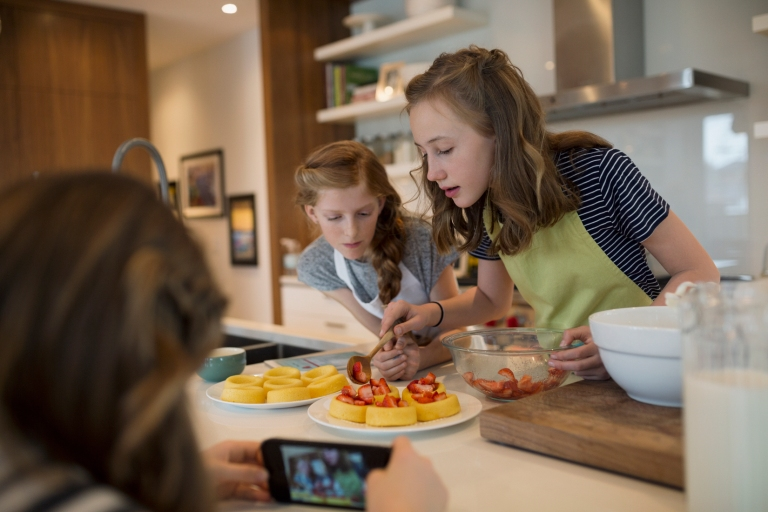 Girl photographing friends making strawberry shortcakes in kitchen