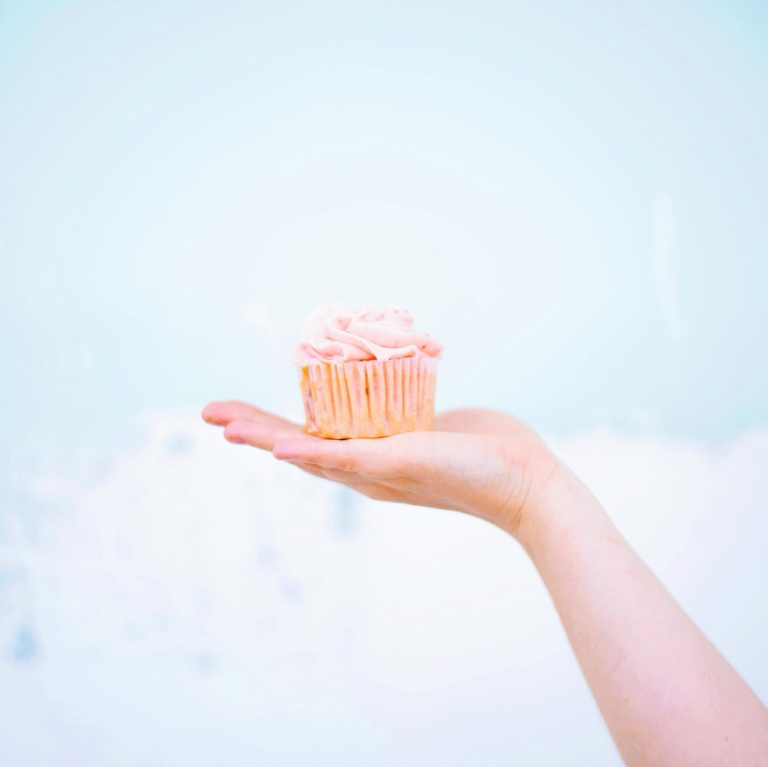Cupcake with pink icing on woman's hand