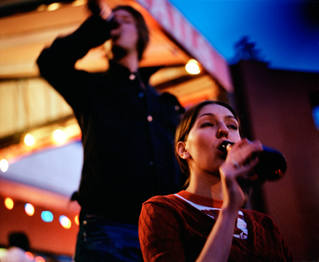 A young man and woman drink bottled beer outdoors