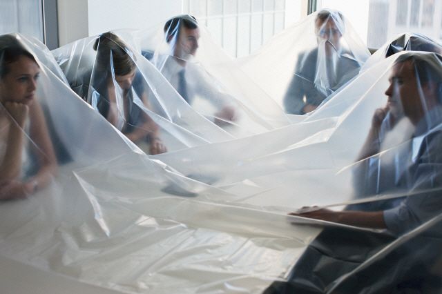Business people covered in plastic in conference room