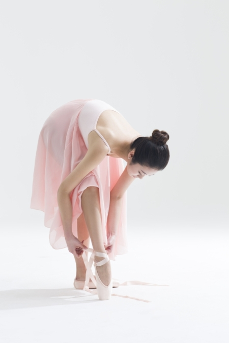 Chinese ballet dancer tying up pointe shoes