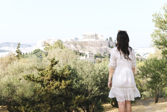 Athens, Greece. Woman looking at The Acropolis and Parthenon of Athens surrounded by olive trees from Areopagus Hill (Mars Hill) .